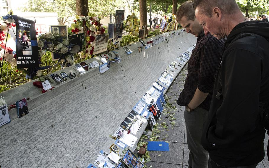 Visitors to the National Law Enforcement Officers Memorial in Washington, D.C. on May 14, 2019, during National Police Week, look at names on the marble memorial to the fallen.