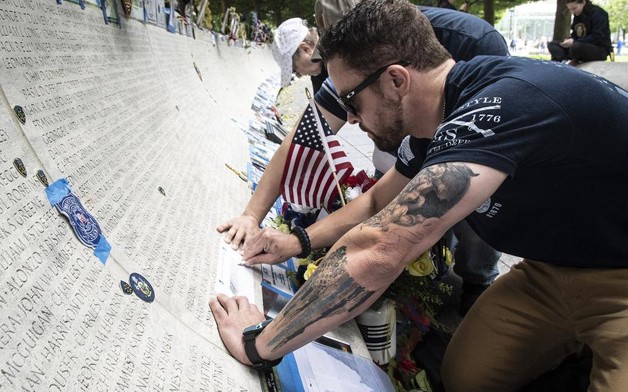Visitors to the National Law Enforcement Officers Memorial in Washington, D.C. on May 14, 2019, during National Police Week, make pencil rubbings of names on the marble memorial to the fallen.