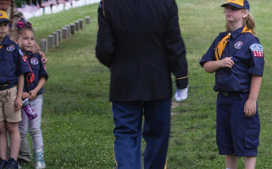 Scouts watch as retired Army Staff Sgt. J.B. Greear walks away after playing taps at the 24th annual luminaria at Fredericksburg National Cemetery in Fredericksburg, Va., May 25, 2019.
