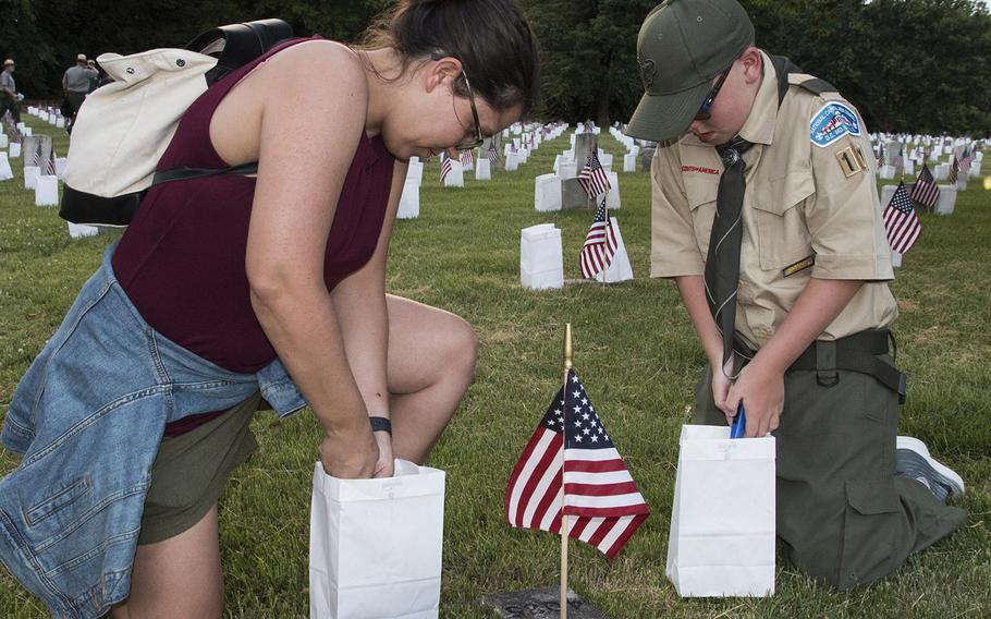 Lindsey Rabun of Norfolk, Va., and son Elijah, 11, light candles during the 24th annual luminaria at Fredericksburg National Cemetery in Fredericksburg, Va., May 25, 2019.