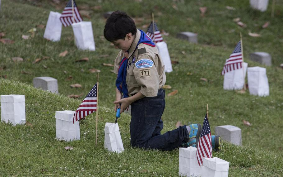 A Boy Scout lights a candle during the 24th annual luminaria at Fredericksburg National Cemetery in Fredericksburg, Va., May 25, 2019.