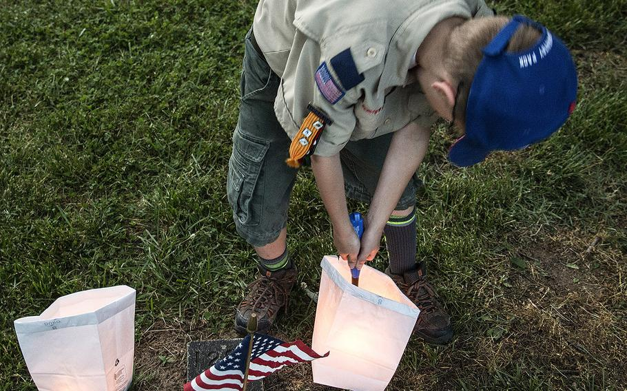 A Scout lights a candle during the 24th annual luminaria at Fredericksburg National Cemetery in Fredericksburg, Va., May 25, 2019.