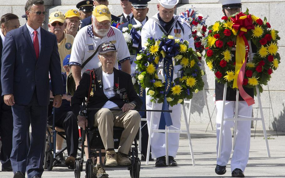 Army veteran Herman Zietchik, center, who stormed Utah Beach with the 4th Infantry Division on D-Day 75 years ago, prepares to place a wreath at the National World War II Memorial in Washington on Memorial Day, May 27, 2019.