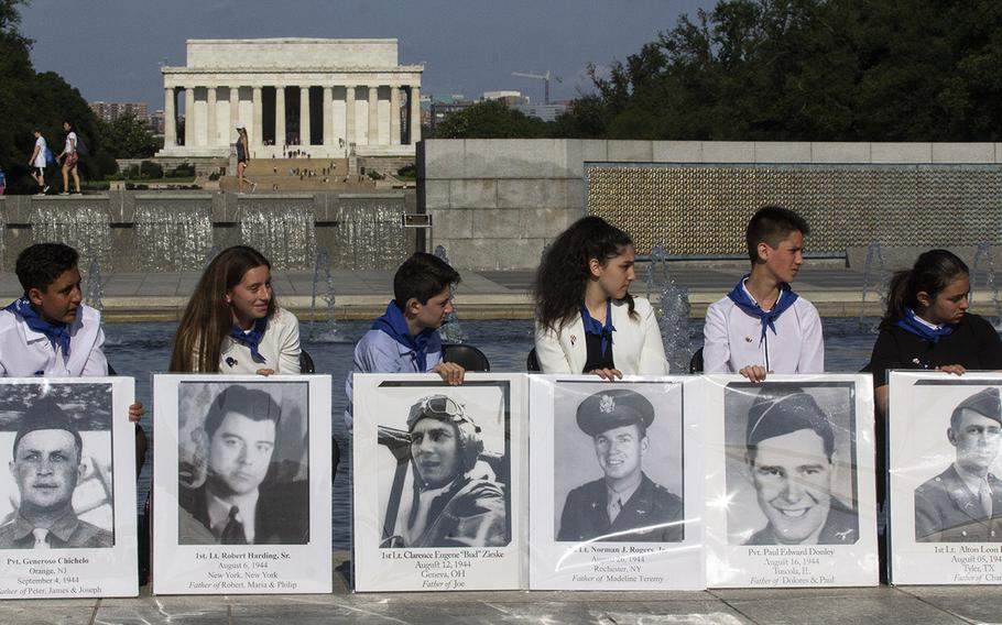 Children hold placards with photos of the fallen on Memorial Day at the National World War II Memorial in Washington, D.C., May 27, 2019.