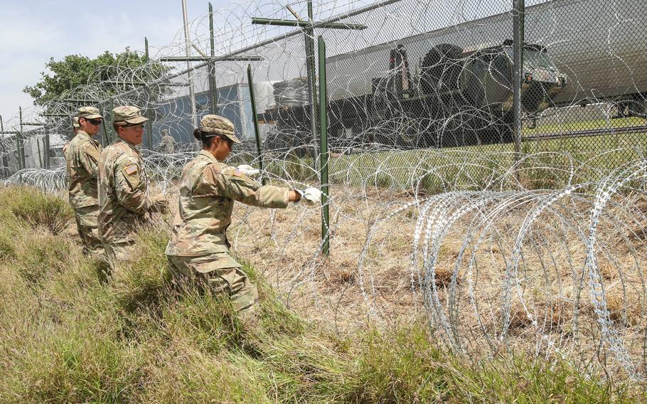 Soldiers from the 161st Engineer Support Company (Airborne) stretch out concertina wire used to secure the existing border fence near the World Trade International Bridge in Laredo, Texas, April 11, 2019.