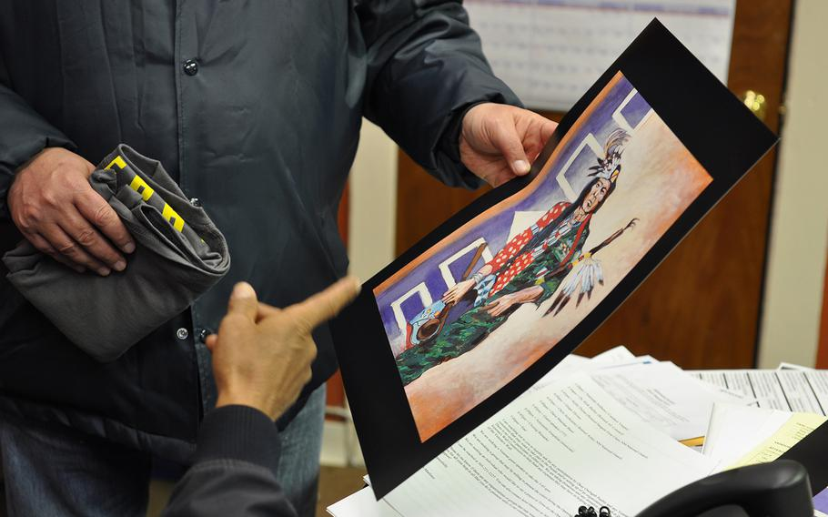 Paul Sullivan, who works in veteran outreach for the law firm Bergmann & Moore, picks up artwork Wednesday, Nov. 7, 2018, depicting a Native American servicemember. Prior to the 9/11 terrorist attacks, American Indians served in the military at a higher rate than veterans of any other race, according to VA data.