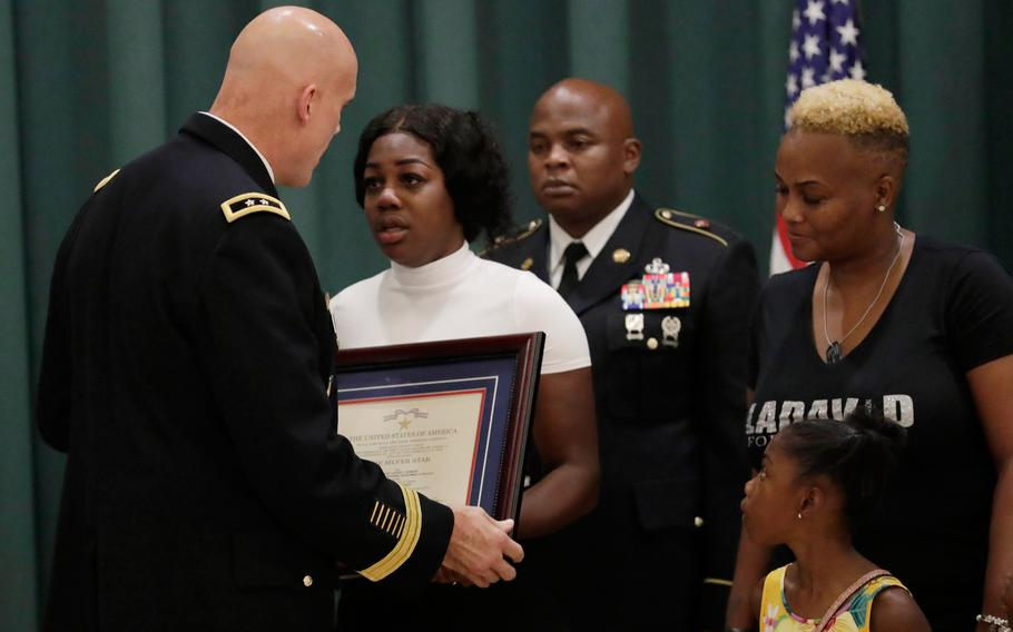 Maj. Gen. John Deedrick, left, presents a plaque to Myeshia Johnson, the widow of Sgt. LaDavid Johnson, during a ceremony awarding the Silver Star Medal to LaDavid Johnson, Friday, Aug. 16, 2019, in Miami Gardens, Fla. Johnson was killed in action during operations in Niger in 2017. At right is LaDavid Johnson's' mother Cowanda Jones- Johnson, and daughter Ahleesya.