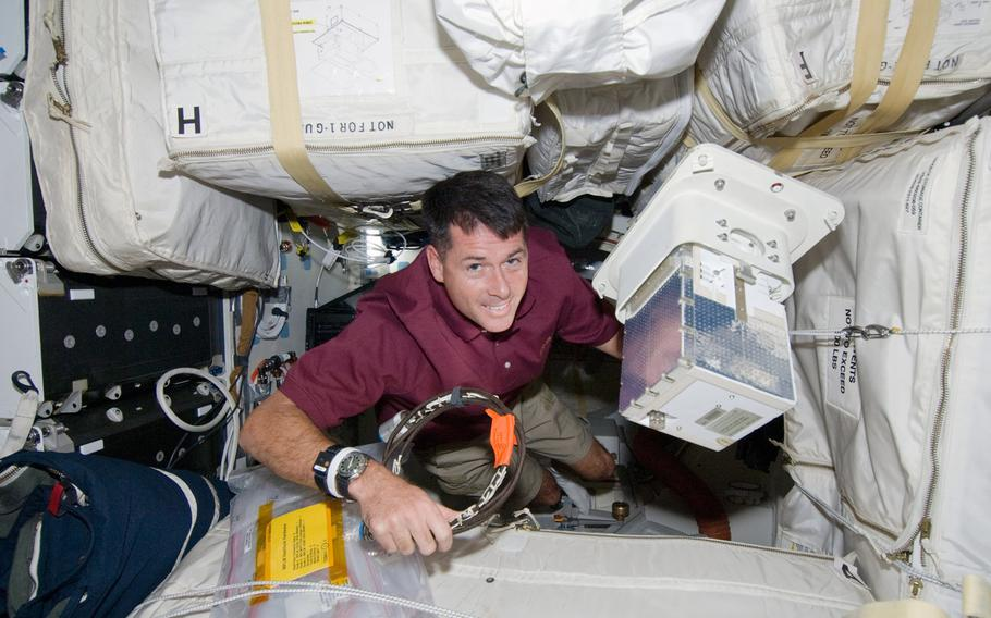 Mission specialist Shane Kimbrough moves equipment among stowage bags on the mid-deck of the orbiter Endeavour on mission STS-126. Kimbrough is a retired Army colonel.
