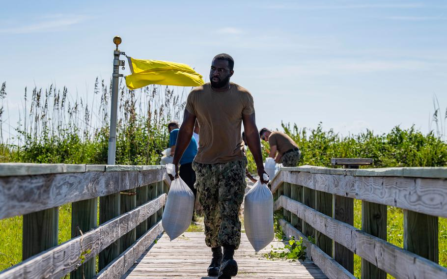 Ship's Serviceman 1st Class Carl Miller carries sand bags on Naval Station Mayport in preparation for Hurricane Dorian on August 29, 2019.