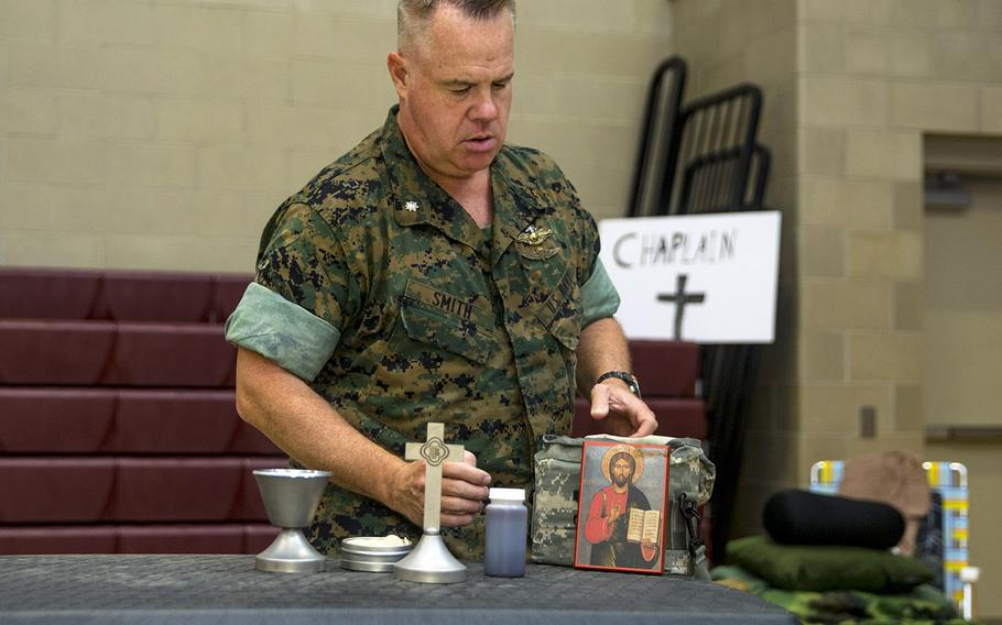 U.S. Navy Cmdr. Patrick W. Smith, chaplain, Marine Corps Air Station New River, prepares an altar at the New River Fitness Center, which is serving as a hurricane shelter on MCAS New River, N.C., Sept. 5, 2019.
