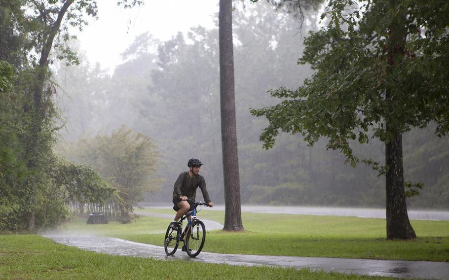 A bike rider travels along a trail in light rain ahead of Hurricane Dorian at Marine Corps Base Camp Lejeune, N.C.