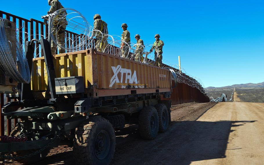 U.S. military personnel help fortify a border barrier in Sasabe, Arizona, on Feb. 7, 2019.