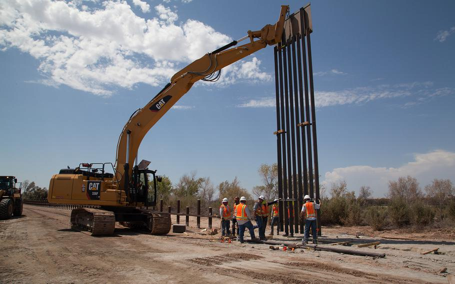 A U.S. Army Corps of Engineers Task Force Barrier contractor installs the first barrier panel at the Yuma project site, near Yuma, Ariz., on Sept. 5, 2019. Pentagon officials confirmed on Wednesday, Sept. 11, that Defense Secretary Mark Esper has approved troop deployments along the US-Mexico border through 2020.