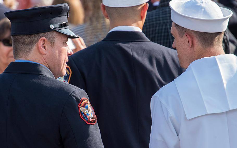 A U.S. Navy sailor speaks with a New York Fire Department firefighter on Wednesday, Sept. 11, 2019 at the Pentagon during a ceremony marking the 18th anniversary of the 9/11 terrorist attacks.