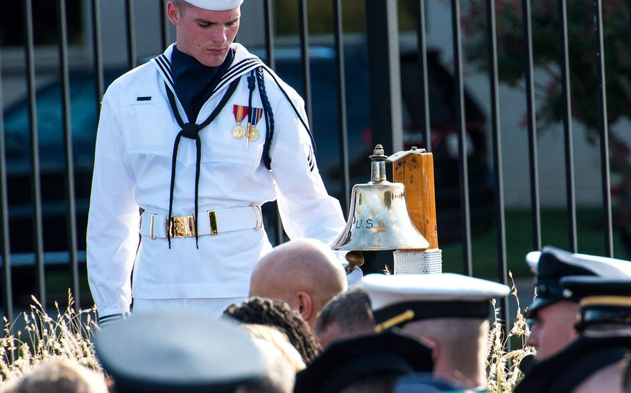 A U.S. Navy sailor rings a bell as names of 184 victims of the 9/11 terrorist attacks at the Pentagon are read aloud on Wednesday, Sept. 11, 2019 during a ceremony marking the 18th year since the attack.