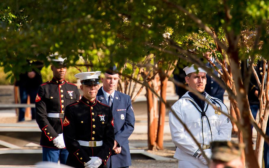 U.S. servicemembers stand among the trees and benches of the Pentagon's 9/11 memorial on Wednesday, Sept. 11, 2019 during a ceremony marking the 18th anniversary of the terrorist attacks.