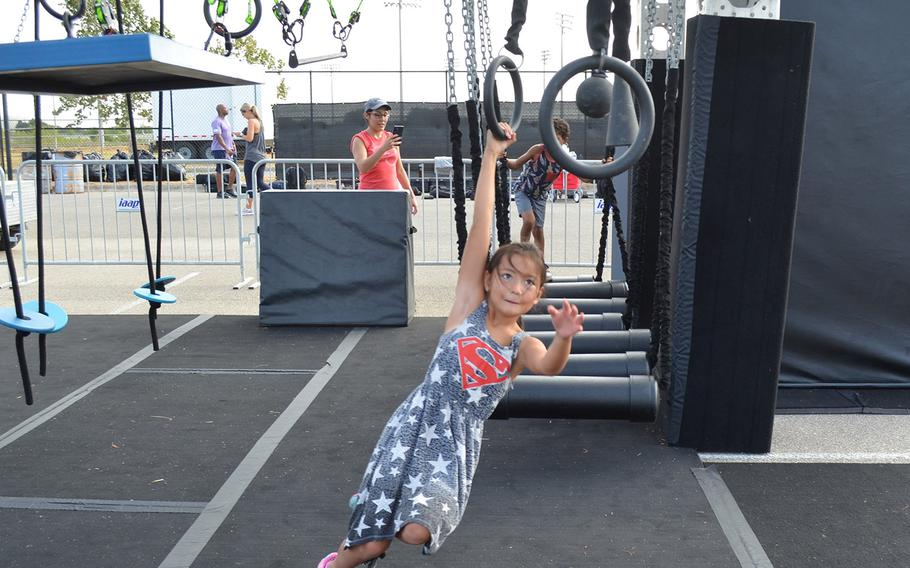 """Kyndra Golloway, 8, plays on a children's version of an Alpha Warrior """"battle rig"""" while waiting for her father, Air Force Staff Sgt. Seth Golloway of Hurlburt Field, Fla., to compete at the Alpha Warrior Proving Ground in San Antonio on Thursday."""