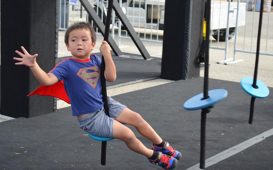 """Lincoln Golloway, 4, plays on a children's version of an Alpha Warrior """"battle rig"""" while waiting for her father, Air Force Staff Sgt. Seth Golloway of Hurlburt Field, Fla., to compete at the Alpha Warrior Proving Ground in San Antonio on Thursday."""