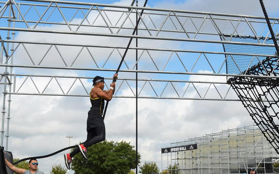 """Army 2nd Lt. Chris Gabayan of Fort Bragg, N.C., swings through an obstacle at the Alpha Warrior Proving Ground in San Antonio on Thursday. Gabayan has made two appearances on the TV show """"American Ninja Warrior,"""" which is a similar style athletic competition."""