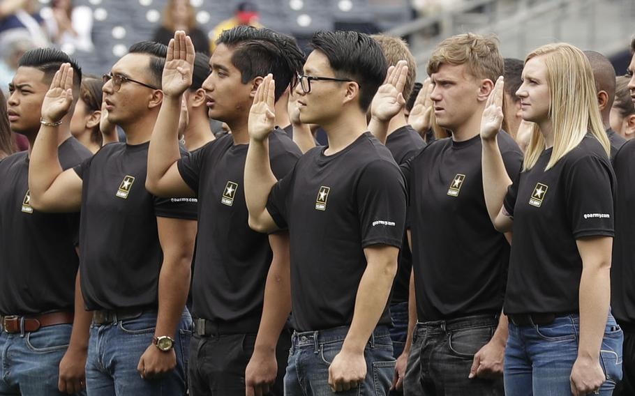 New Army recruits take part in a swearing-in ceremony before a baseball game between the San Diego Padres and the Colorado Rockies in San Diego. A year after failing to meet its enlistment goal for the first time in 13 years, the U.S. Army is now on track to meet a lower 2019 target after revamping its recruitment effort.