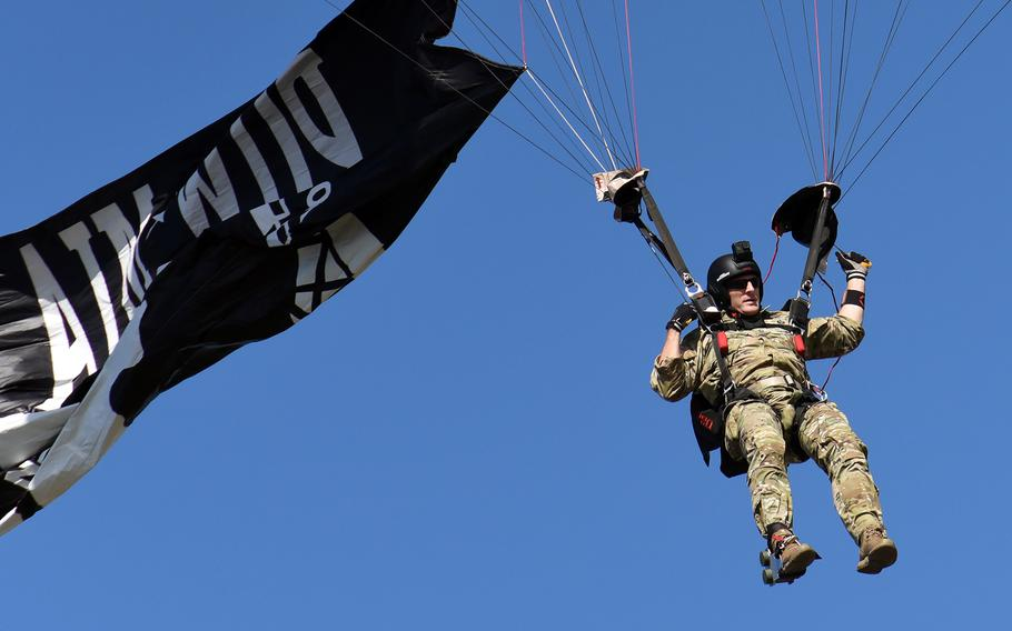 U.S. Army Master Sgt. Chris Malone, of the U.S. Army Special Operations Command Black Daggers parachute team, flies the Prisoner of War/Missing in Action flag as he jumps over the Pentagon on Friday, Sept. 20, 2019 during the National POW/MIA Recognition Ceremony.