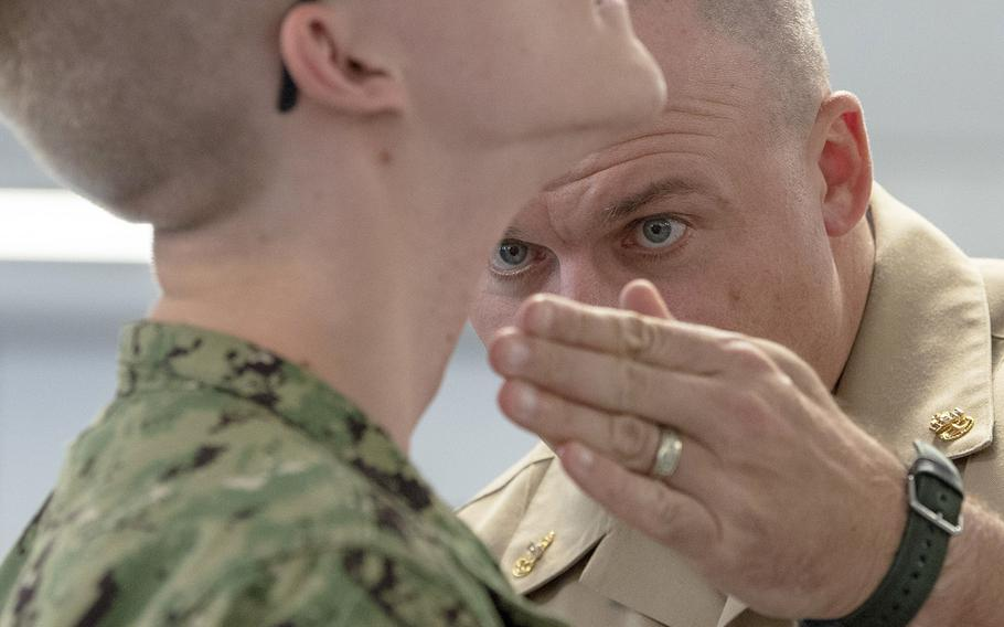 In an October, 2018 file photo, Chief Operations Specialist James Conyne, a recruit division commander, inspects the quality of a recruit's shave before a personnel inspection inside a compartment in the USS Kearsarge barracks at Recruit Training Command in Great Lakes, Ill.