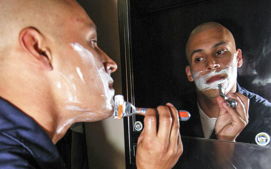 Lt. Gierag Andrews shaves in his stateroom before assuming the watch aboard the submarine USS Henry M. Jackson.