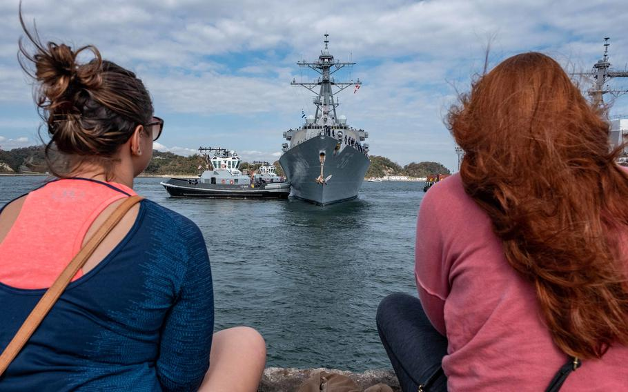 Onlookers sit on a pier as the USS John S. McCain departs Yokosuka, Japan, Oct. 28, 2019, to conduct comprehensive at-sea testing, the ship's first underway since its collision in 2017.