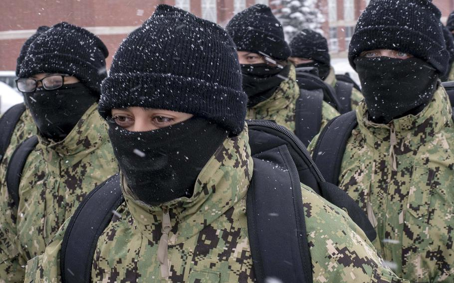 In a January, 2019 photo, recruits walk in formation wearing neck gaiters during a snowstorm at Recruit Training Command in Great Lakes, Ill..