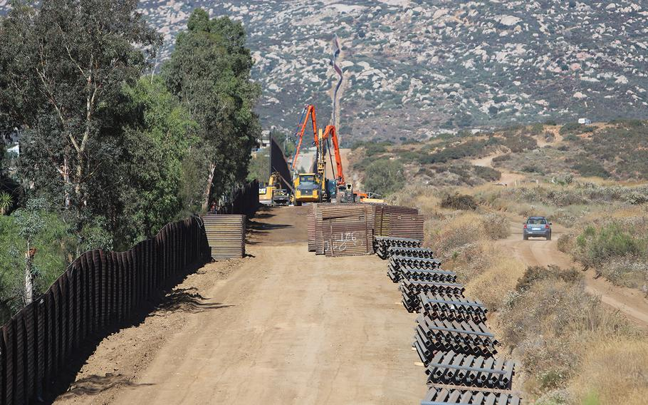 U.S. Army Corps of Engineers contractors place and align concrete-filled bollards at Tecate, CalifornIa on Aug. 9, 2019.