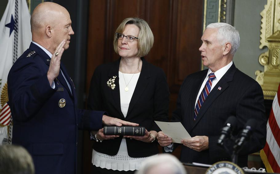 Vice President Mike Pence, right, swears in Air Force General John Raymond as Chief of Space Operations, as his wife, Molly, center, holds a bible in the Vice President's Ceremonial Office at the Executive Office Building, Tuesday, Jan. 14, 2020 in Washington.