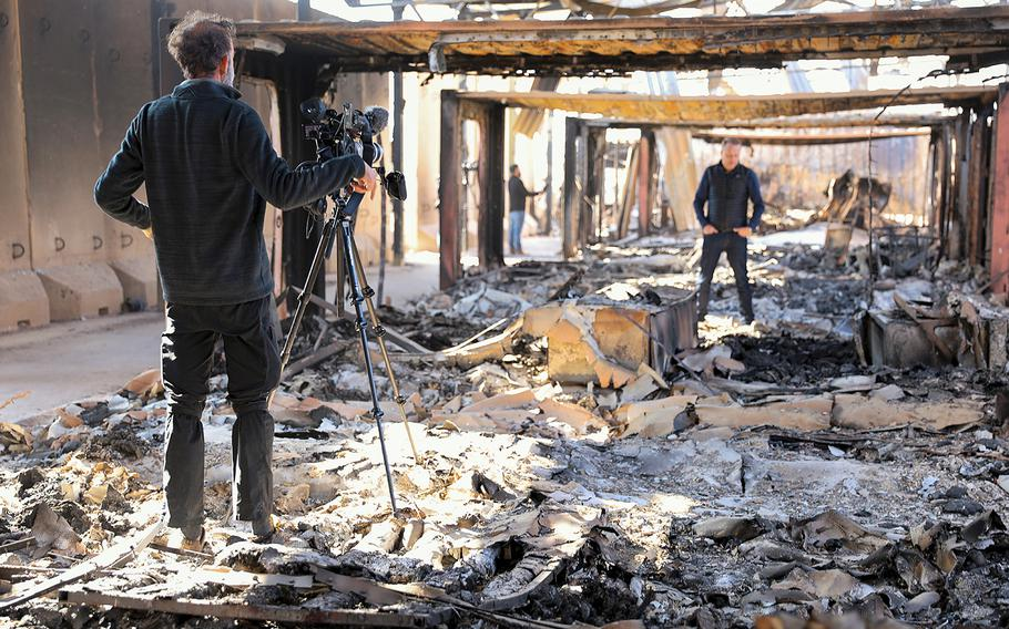"""News agencies report from destroyed living quarters at Al Asad Air Base, Iraq, on Jan. 13, 2020, after missile attacks were launched by Iran. President Donald Trump said on Wednesday, Jan. 22, that he was informed that some U.S. troops suffered """"headaches and a couple of other things. I can report it is not very serious."""""""