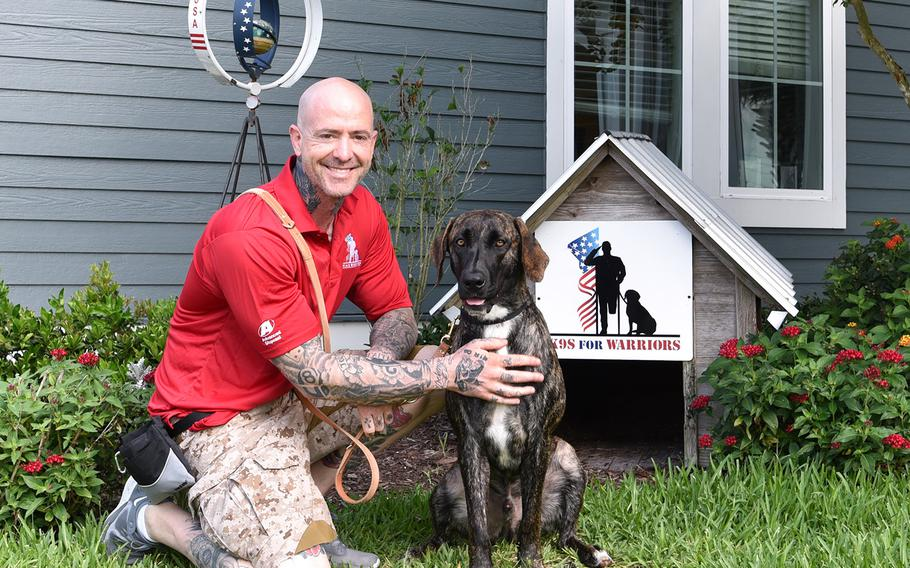 Damian Jungermann, 45, kneels with his service dog Shai, who turns two years old in March.