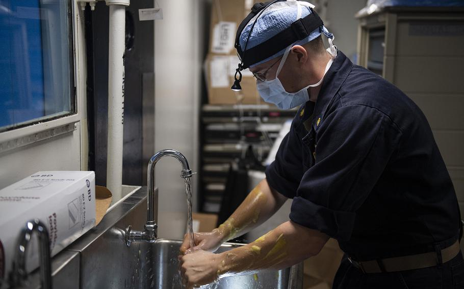 Lt. Cmdr. Justin Miller, a Navy surgeon washes his hands in preparation for surgery outside an operating room aboard the amphibious assault ship USS Wasp (LHD 1) while deployed in the Coral Sea on June 28, 2019.