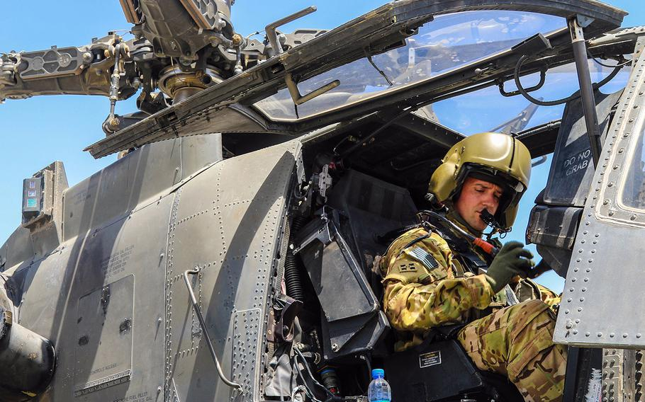 A U.S. Army AH-64 Apache pilot conducts final preflight checks before taking off in Afghanistan in April 2019. The Army announced new bonuses for pilots to try to keep them from being lured away by higher pay and better benefits paid by commercial airlines.