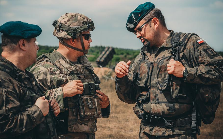 U.S. Army Chief Warrant Officer 2 Eric Land, center, assigned to 5th Battalion, 7th Air Defense Regiment, talks with Polish air defense artillery officers about the new MIM-104 Patriot surface-to-air missile system near Drawsko Pomorskiego, Poland, in June 2018. The Army is offering big bonuses to lure more warrant officers into the air defense artillery branch.