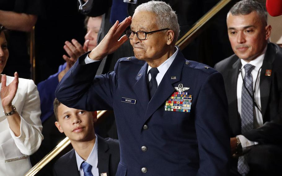 Tuskegee airman Charles McGee, 100, salutes as his great grandson Iain Lanphier looks on after President Donald Trump praised McGee for his service during Trump's State of the Union address to a joint session of Congress on Capitol Hill in Washington, Tuesday, Feb. 4, 2020.
