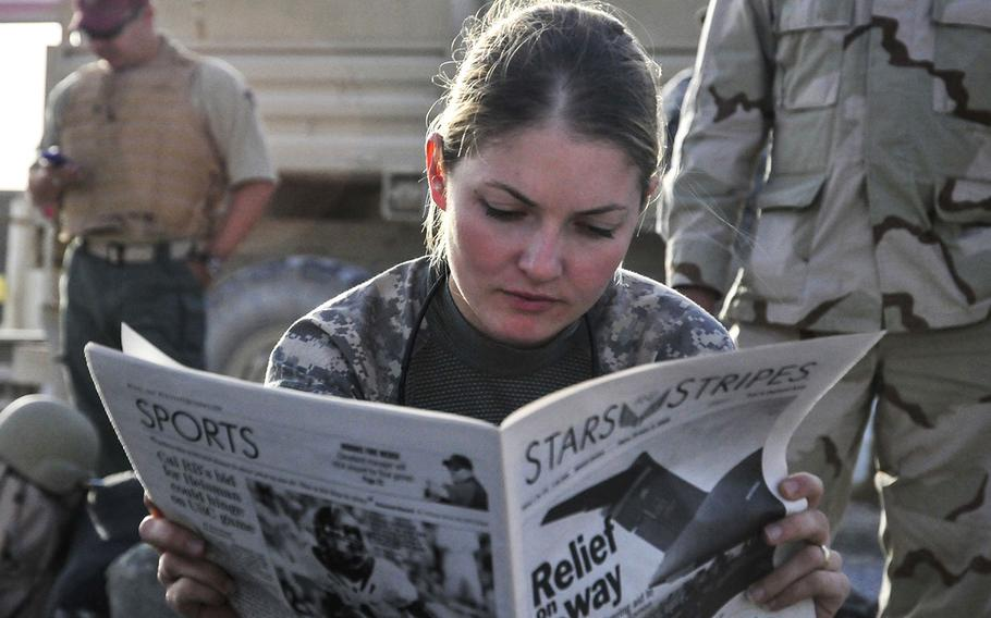U.S. Army 1st Lt. Tracy Tyson, with 5th Brigade Combat Team, 2nd Infantry Division, reads the Stars and Stripes newspaper at Kandahar Airfield, Afghanistan, Oct. 5, 2009, while waiting for a flight to Forward Observation Base Wolverine.