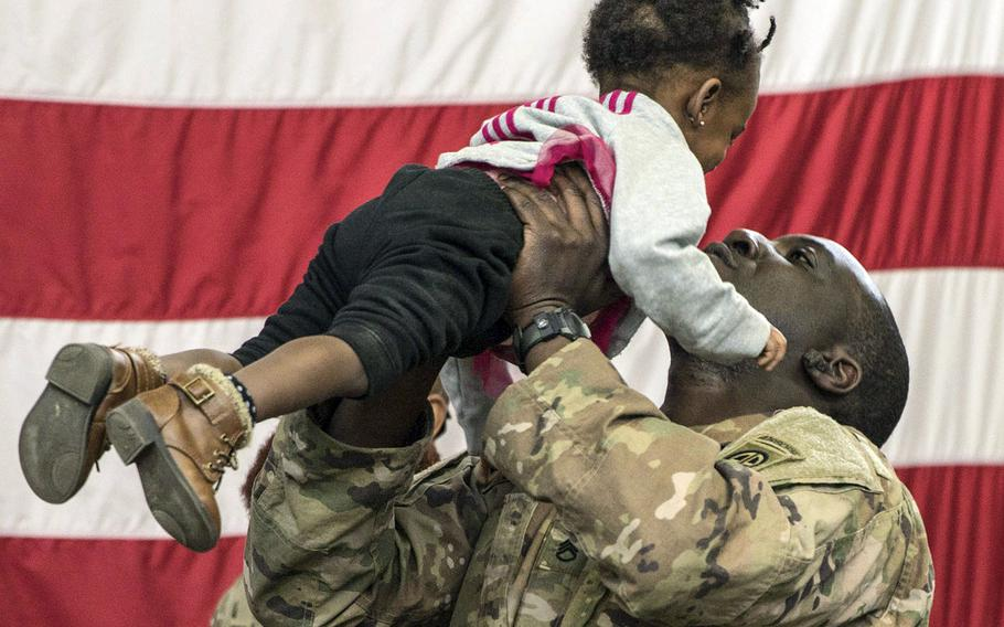 A paratrooper from 1st Brigade Combat Team, 82nd Airborne Division holds his daughter during a redeployment ceremony at Fort Bragg, N.C., February 20, 2020.