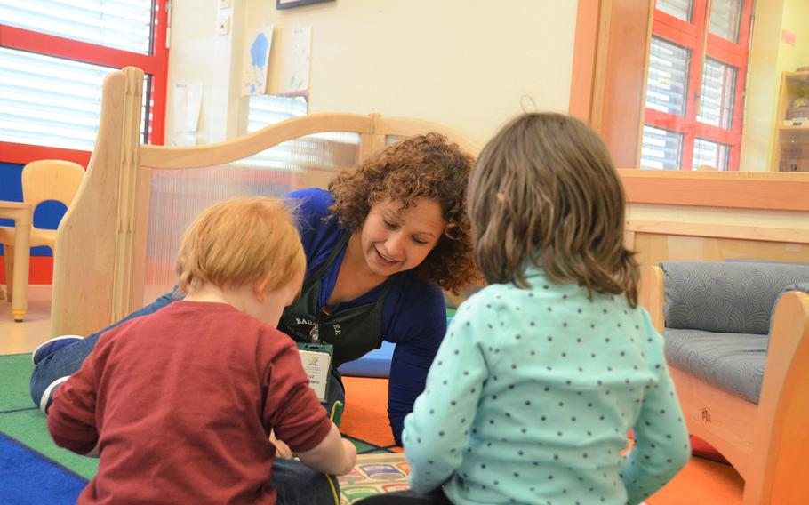A Smith Child Development Center caregiver interacts with children in a play group in Baumholder, Germany on April 28, 2018.