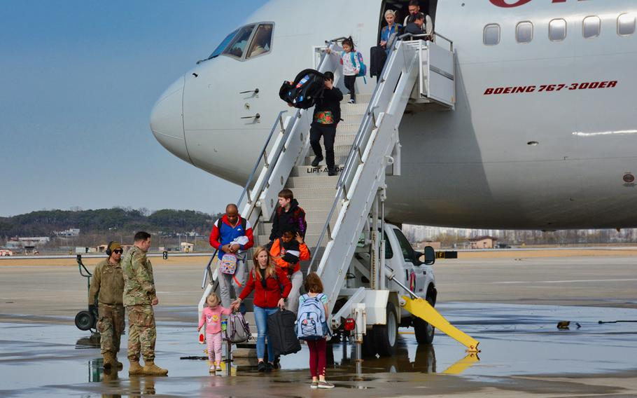 American troops and family members arrive on Osan Air Base, South Korea, on Friday, March 13, 2020, days after they were kicked off a military charter flight in Seattle amid confusion over an Army order halting moves amid the coronavirus crisis.