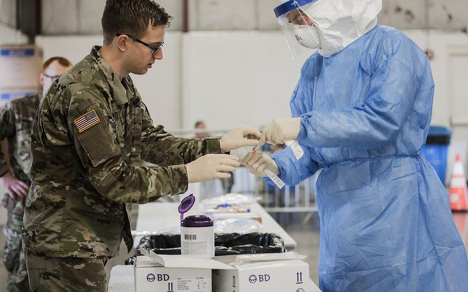 U.S. Army Spc. Gabriel Eiter, left, a small arms/artillery repairer assigned to the 3637th Maintenance Company, Illinois Army National Guard, and Lt. Col. Jim Avery, a flight surgeon assigned to the 126th Medical Group, Illinois Air National Guard, handles COVID-19 testing equipment at a drive-thru testing site in Bloomington, Ill., March 28, 2020.