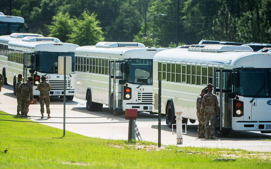 In a June, 2018 photo, drill sergeants at Fort Benning, Ga., stand by as busloads of new recruits pull in to start entry level training.