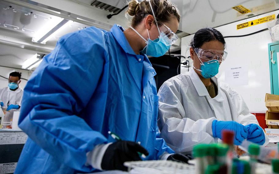 Navy Hospital Corpsman Jackii Cheung, right, and Army Spc. Cortney Elliot, both assigned to the Javits New York Medical Station, process blood samples from COVID-19 patients in the facility's medical laboratory, April 13, 2020.