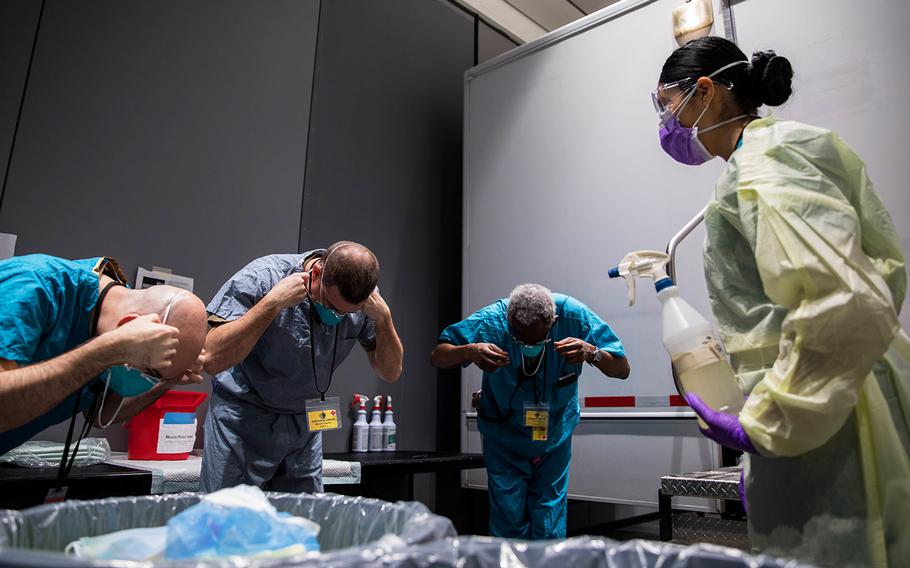 Navy Hospital Corpsman 3rd Class Katie Perez, assigned to Expeditionary Medical Facility Bethesda, Md., leads medical providers in removing their N95 masks in the personal protective equipment doffing station at Javits New York Medical Station, April 13, 2020.