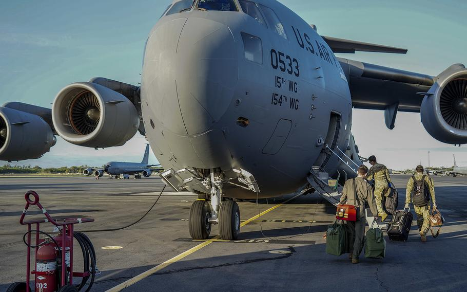 U.S. Air Force 535th Airlift Squadron pilots board a C-17 Globemaster III before taking off to Guam at Joint Base Pearl Harbor-Hickam, Hawaii, April 13, 2020. Defense Department officials announced on Saturday, April 17, that a new directive on the movement of military personnel and their families will bar travel through June 30.