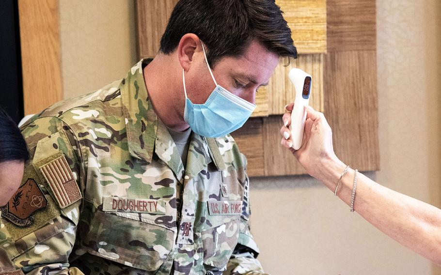 Cpt. Brendan Dougherty gets his temperature checked while filling out a medical screening questionnaire before entering the Broomall Rehabilitation and Nursing Center in Broomall, Pa., on April 18, 2020.