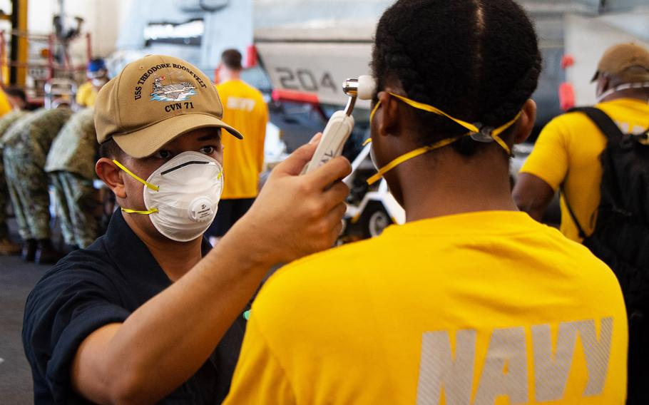 Sailor David Romero takes the temperature of another sailor assigned to the aircraft carrier USS Theodore Roosevelt on April 10, 2020.