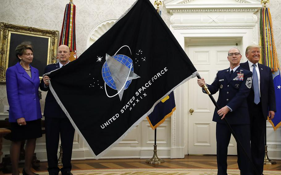 President Donald Trump stands as Chief of Space Operations at US Space Force Gen. John Raymond, second from left, and Chief Master Sgt. Roger Towberman, second from right, hold the United States Space Force flagas it is presented in the Oval Office of the White House, May 15, 2020, in Washington. Secretary of the Air Force Barbara Barrett stands at far left.