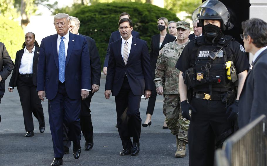 Defense Secretary Mark Esper, center, walks with President Donald Trump and Chairman of the Joint Chiefs of Staff Gen. Mark Milley as they depart the White House on Monday, June 1, 2020, to visit St. John's Church, which was set on fire during protests on Sunday night.